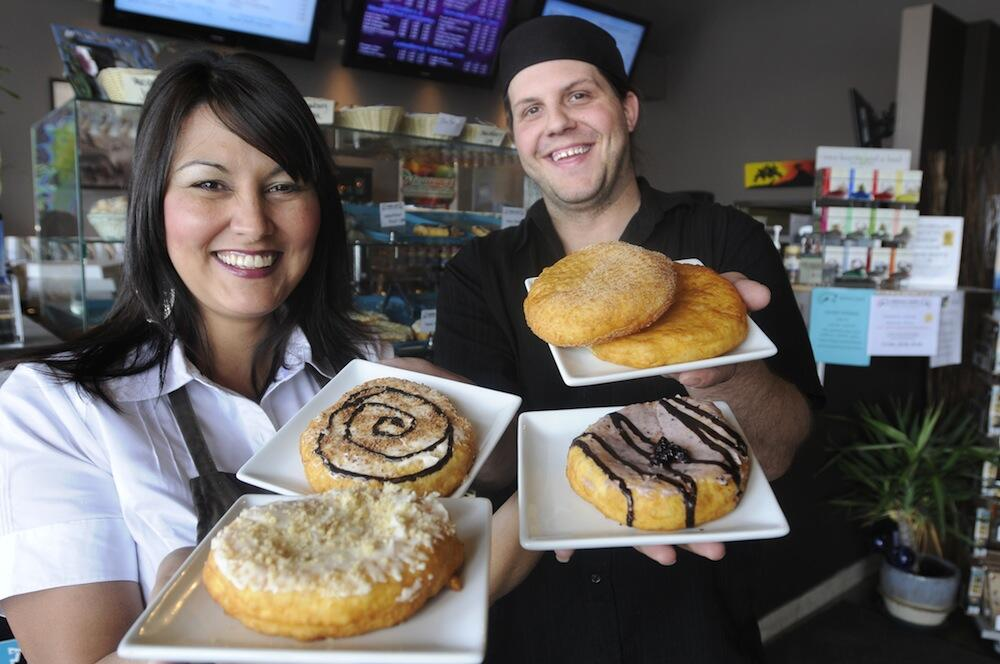 Kekuli Cafe owners Sharon Bond and Darren Hogg holding a variety of plated bannock treats.